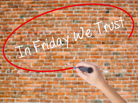 positiveness: Woman Hand Writing In Friday We Trust  with black marker on visual screen. Isolated on bricks. Business concept. Stock Photo Stock Photo