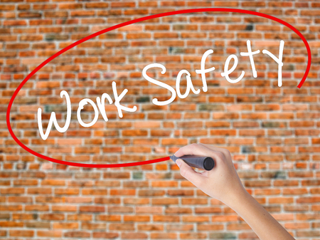 or electrocution: Woman Hand Writing Work Safety with black marker on visual screen. Isolated on bricks. Business concept. Stock Photo