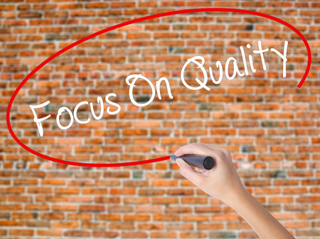 Woman Hand Writing Focus On Quality with black marker on visual screen. Isolated on bricks. Business concept. Stock Photo