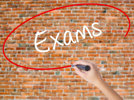 Woman Hand Writing Exams with black marker on visual screen. Isolated on bricks. Business concept. Stock Photo