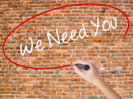 Woman Hand Writing We Need You with black marker on visual screen. Isolated on bricks. Business concept. Stock Photo
