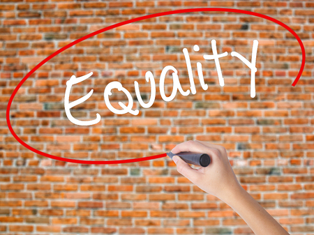 Woman Hand Writing Equality  with black marker on visual screen. Isolated on bricks. Business concept. Stock Photo Stock Photo