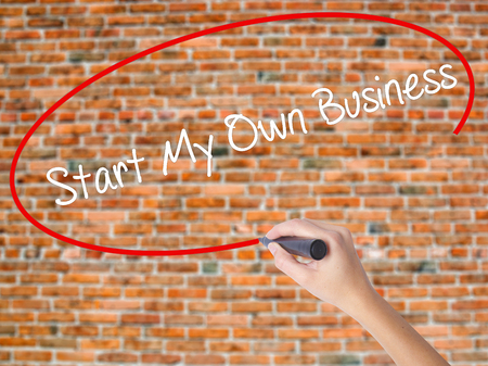 Woman Hand Writing Start My Own Business with black marker on visual screen. Isolated on bricks. Business concept. Stock Photo Stock Photo