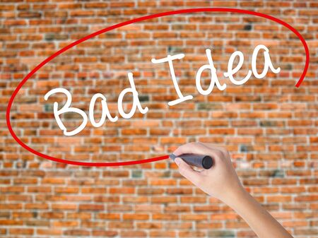 Woman Hand Writing Bad Idea with black marker on visual screen. Isolated on bricks. Business concept. Stock Photo