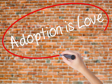 Woman Hand Writing Adoption is Love with black marker on visual screen. Isolated on bricks. Adoption, technology, internet concept. Stock Photo