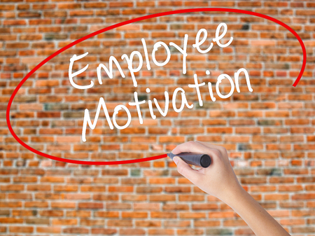 induce: Woman Hand Writing Employee Motivation with black marker on visual screen. Isolated on bricks. Business, technology, internet concept. Stock  Photo