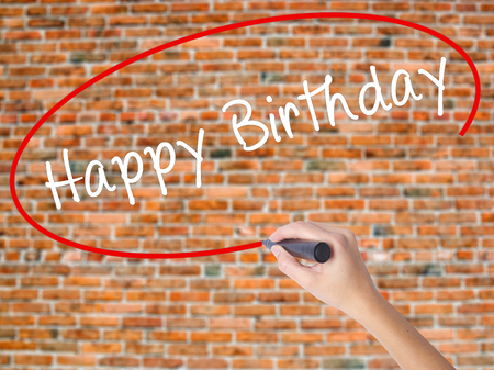 celebratory event: Woman Hand Writing Happy Birthday with black marker on visual screen. Isolated on bricks. Business concept. Stock Photo Stock Photo