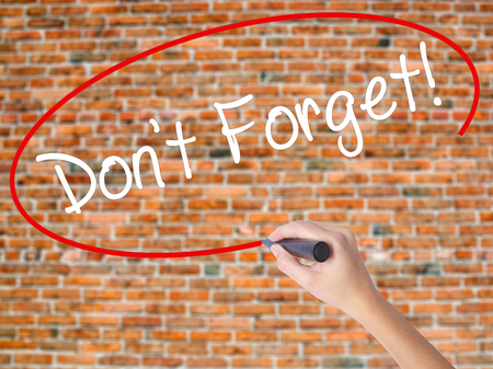 Woman Hand Writing Dont Forget!  with black marker on visual screen. Isolated on bricks. Adoption, technology, internet concept. Stock Photo Stock Photo