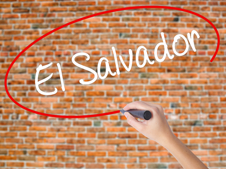 Woman Hand Writing El Salvador with black marker on visual screen. Isolated on bricks. Business concept. Stock Photo