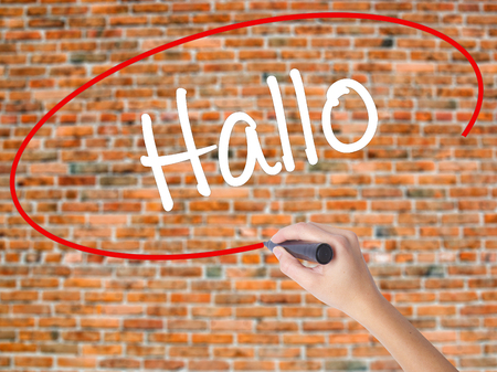 hallo: Woman Hand Writing Hallo  (Hello in German) with black marker on visual screen. Isolated on bricks. Business concept. Stock Photo Stock Photo