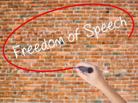 censure: Woman Hand Writing Freedom of Speech with black marker on visual screen. Isolated on bricks. Business concept. Stock Photo