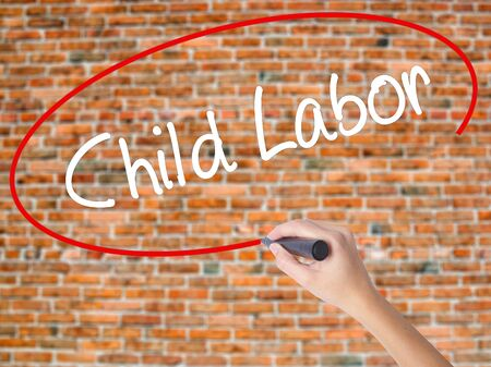 Woman Hand Writing Child Labor with black marker on visual screen. Isolated on bricks. Business concept. Stock Photo