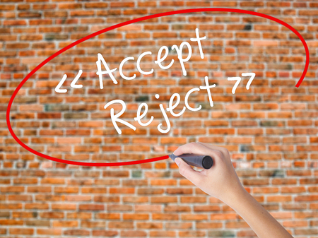 approvement: Woman Hand Writing Accept - Reject  with black marker on visual screen. Isolated on bricks. Business concept. Stock Photo