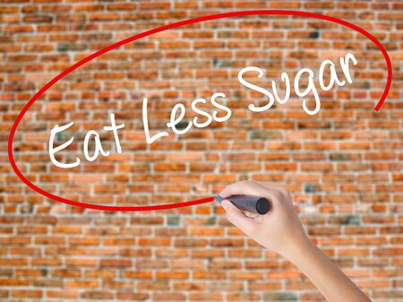 postit note: Woman Hand Writing Eat Less Sugar  with black marker on visual screen. Isolated on bricks. Business concept. Stock Photo
