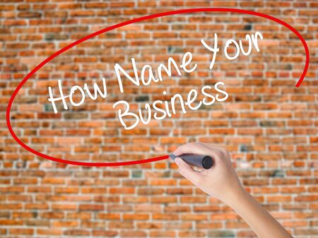 Woman Hand Writing How Name Your Business with black marker on visual screen. Isolated on bricks. Business concept. Stock Photo