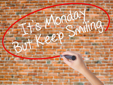 Woman Hand Writing Its Monday But Keep Smiling with black marker on visual screen. Isolated on bricks. Business concept. Stock Photo