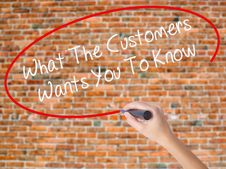 testimonials: Woman Hand Writing What The Customers Wants You To Know with black marker on visual screen. Isolated on bricks. Business concept. Stock Photo