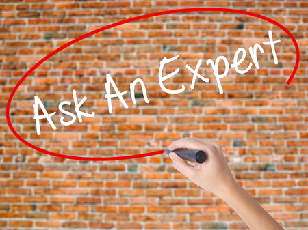 warranty questions: Woman Hand Writing Ask An Expert with black marker on visual screen. Isolated on bricks. Business concept. Stock Photo Stock Photo