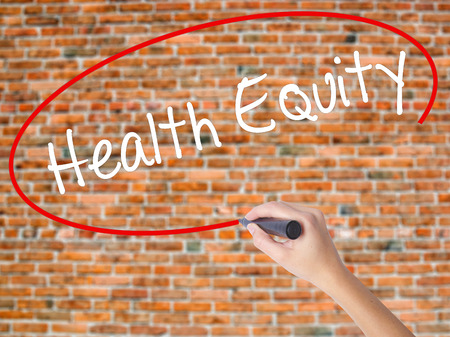 health equity: Woman Hand Writing Health Equityt with black marker on visual screen. Isolated on bricks. Business concept. Stock Photo