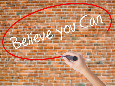 Woman Hand Writing Believe you Can with black marker on visual screen. Isolated on bricks. Business concept. Stock Photo