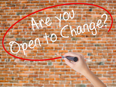 Woman Hand Writing Are you Open to Change? with black marker on visual screen. Isolated on bricks. Business concept. Stock Photo