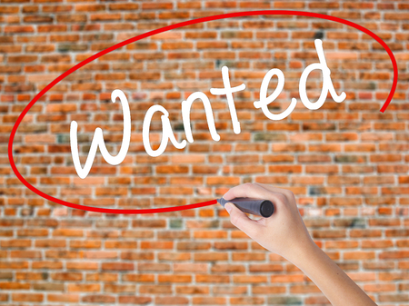 Woman Hand Writing Wanted with black marker on visual screen. Isolated on bricks. Business concept. Stock Photo