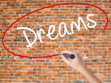 Woman Hand Writing Dreams with black marker on visual screen. Isolated on bricks. Business concept. Stock Photo