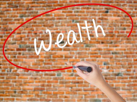 Woman Hand Writing Wealth with black marker on visual screen. Isolated on bricks. Business concept. Stock Photo Stock Photo