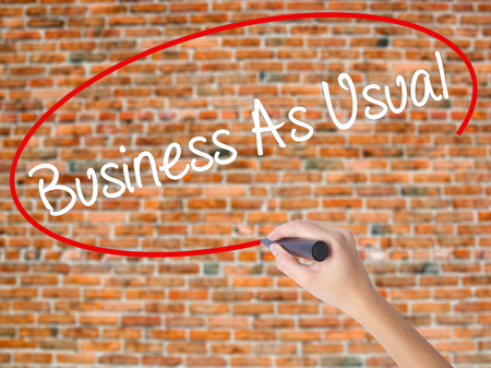 Woman Hand Writing Business As Usual with black marker on visual screen. Isolated on bricks. Business concept. Stock Photo