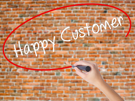 Woman Hand Writing Happy Customer with black marker on visual screen. Isolated on bricks. Business concept. Stock Photo