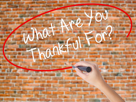 Woman Hand Writing What Are You Thankful For? with black marker on visual screen. Isolated on bricks. Business, technology, internet concept. Stock Photo