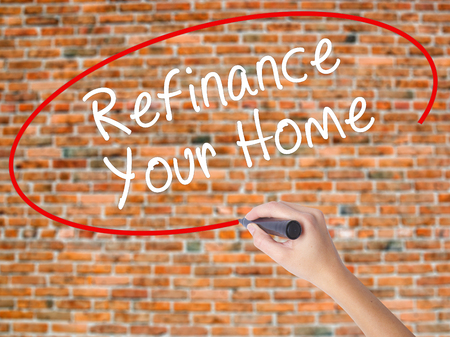 Woman Hand Writing Refinance Your Home with black marker on visual screen. Isolated on bricks. Business concept. Stock Photo Stock Photo
