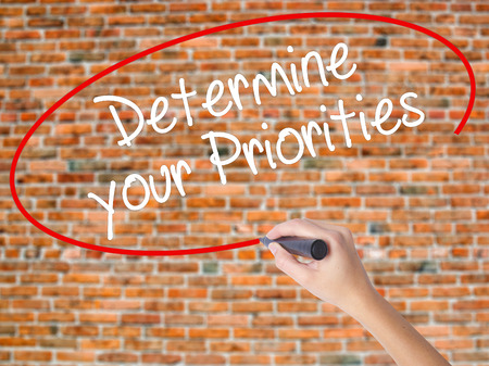 Woman Hand Writing Determine your Priorities with black marker on visual screen. Isolated on bricks. Business concept. Stock Photo