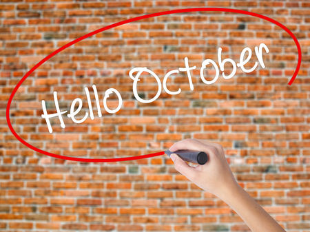 Woman Hand Writing  Hello October  with black marker on visual screen. Isolated on bricks. Business concept. Stock Photo Stock Photo