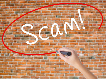 Woman Hand Writing  Scam! with black marker on visual screen. Isolated on bricks. Business concept. Stock Photo Stock Photo