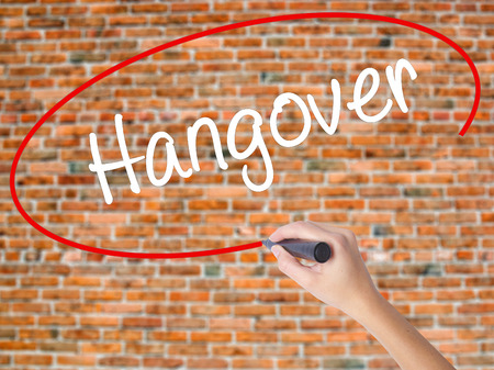 Woman Hand Writing Hangover with black marker on visual screen. Isolated on bricks. Business concept. Stock Photo Stock Photo