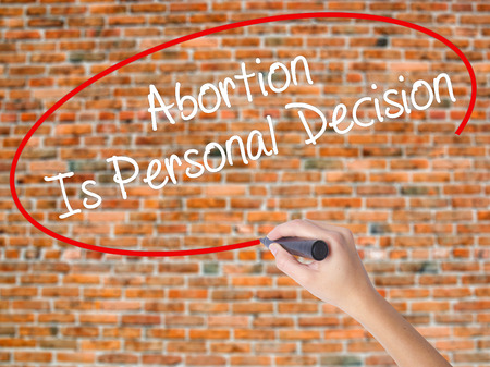 Woman Hand Writing Abortion Is Personal Decision with black marker on visual screen. Isolated on bricks. Business concept. Stock Photo Stock Photo