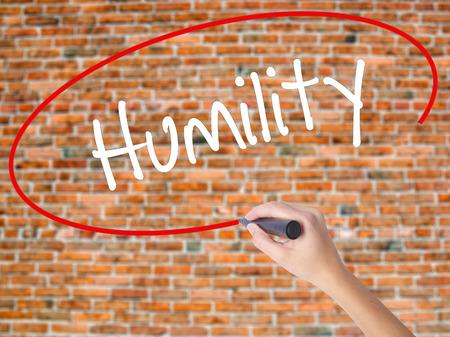 soltería: Mujer escritura de la mano Humildad con marcador negro en la pantalla visual. Aislados en ladrillos. Concepto de negocio. Foto de stock