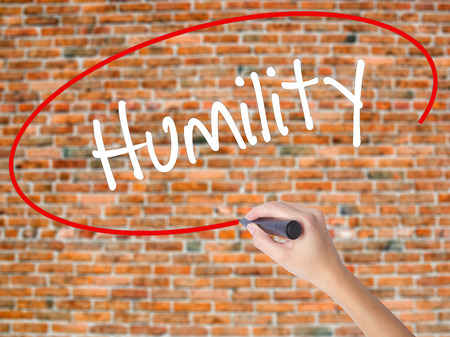 humildad: Woman Hand Writing Humility  with black marker on visual screen. Isolated on bricks. Business concept. Stock Photo