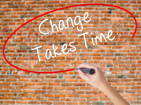 Woman Hand Writing Change Takes Time with black marker on visual screen. Isolated on bricks. Business concept. Stock Photo