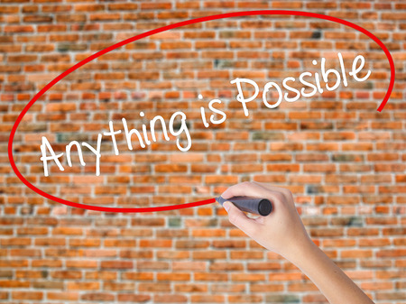Woman Hand Writing Anything is Possible with black marker on visual screen. Isolated on bricks. Business concept. Stock Photo