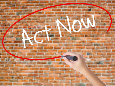 Woman Hand Writing Act Now with black marker on visual screen. Isolated on bricks. Business concept. Stock Photo Stock Photo