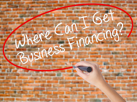 Woman Hand Writing Where Can I Get Business Financing? with black marker on visual screen. Isolated on bricks. Business concept. Stock Photo Stock Photo