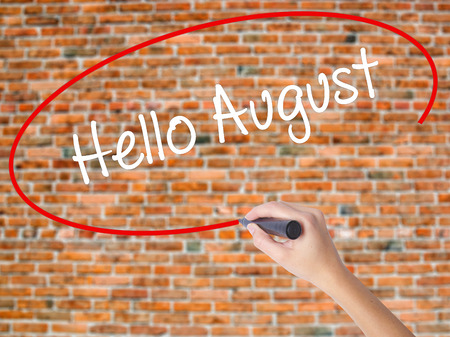 Woman Hand Writing Hello August with black marker on visual screen. Isolated on bricks. Business concept. Stock Photo