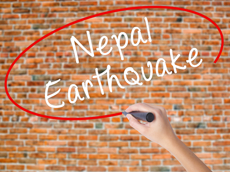 quake: Woman Hand Writing Nepal Earthquake with black marker on visual screen. Isolated on bricks. Business concept. Stock Photo Stock Photo