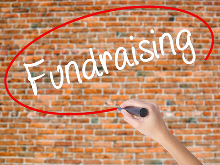 Woman Hand Writing Fundraising with black marker on visual screen. Isolated on bricks. Business concept. Stock Photo
