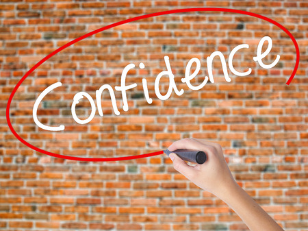 Woman Hand Writing Confidence with black marker on visual screen. Isolated on bricks. Business concept. Stock Photo