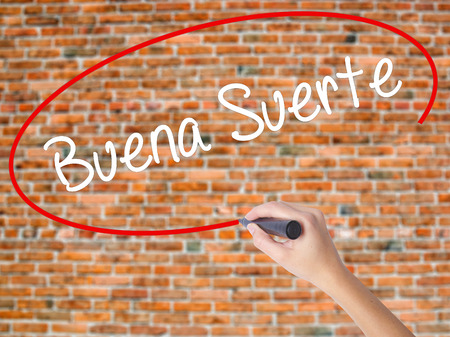 Woman Hand Writing Buena Suerte( Good Luck in Spanish) with black marker on visual screen. Isolated on bricks. Business concept. Stock Photo Stock Photo