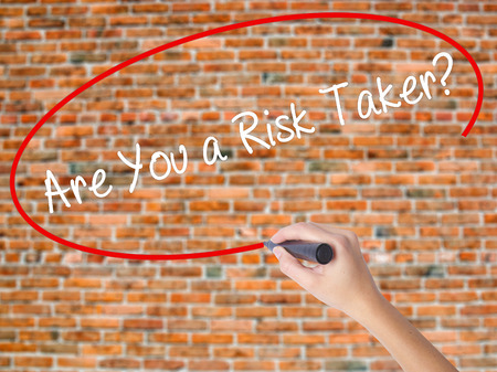 taker: Woman Hand Writing Are You a Risk Taker? with black marker on visual screen. Isolated on bricks. Business concept. Stock Photo