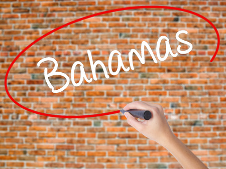 Woman Hand Writing Bahamas with black marker on visual screen. Isolated on bricks. Business concept. Stock Photo